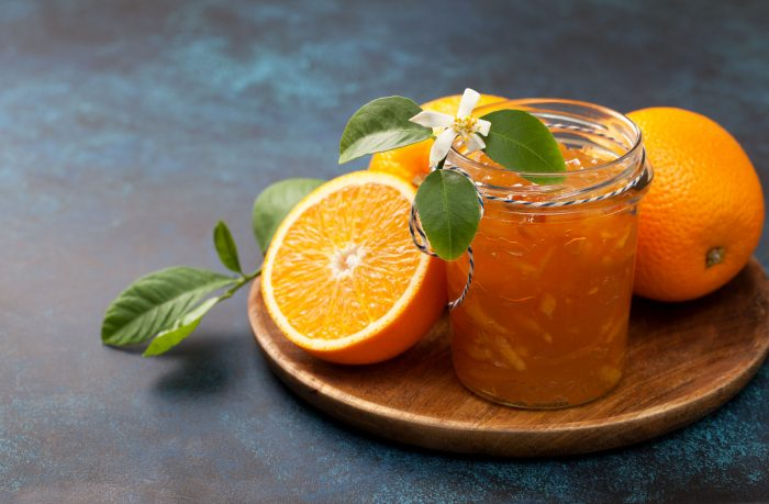 88714157 - orange jam in a glass jar, fresh oranges on a wooden plate on a blue background
