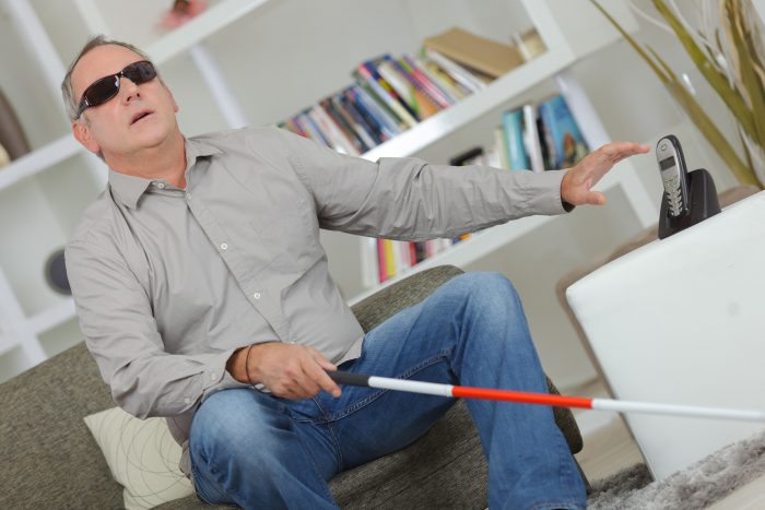 78707049 - blind and deaf man using stick at home