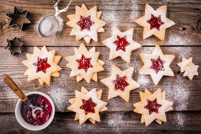 68883693 - christmas linzer cookies with raspberry jam on a rustic wooden background