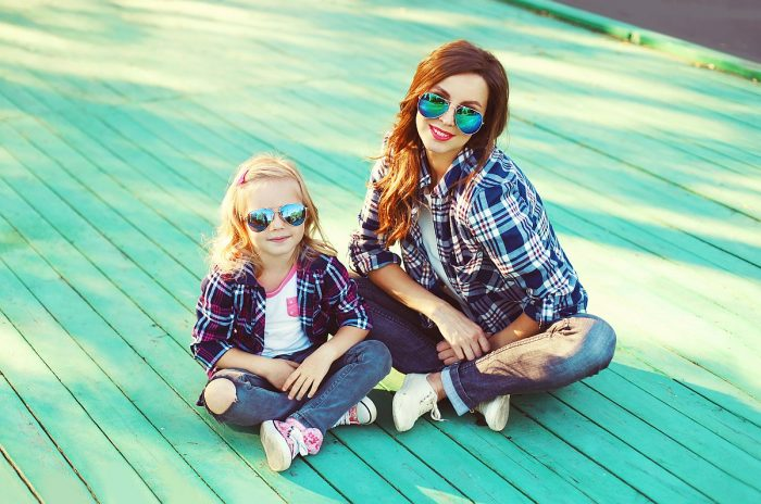 Fashion mother and child daughter wearing a sunglasses and checkered shirt sitting in city